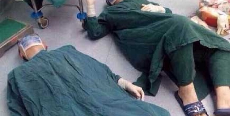 Foto ar uz grīdas guļošiem ķirurgiem pārsteidza visus. Iemesls nevienu neatstās vienaldzīgu!